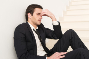 Tired and depressed. Side view of depressed young man in formalw